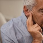 Side view of senior man with symptom of hearing loss. Mature man sitting on couch with fingers near ear suffering pain.